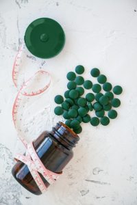 tape measure with bottle of green spirulina pills